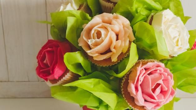 白い木製の机の上のケーキとカップケーキで作られた花の花束のクローズ アップ写真。白い背景の上のお菓子とペストリーの美しいショット