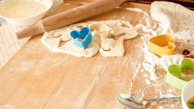 大きな木製のキッチン カウンター ボードに横になっているパン屋や料理のための新鮮な生地、卵、牛乳、および多くのツールのクローズ アップ写真
