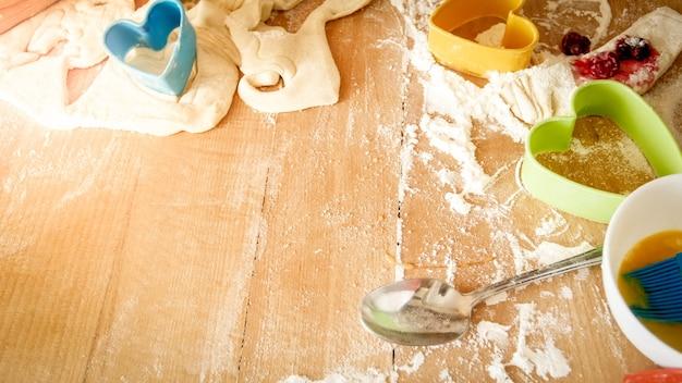 大きな木製のキッチンのカウンターボードに横たわっている新鮮な生地、卵、牛乳、そしてパン屋と料理のためのたくさんの道具のクローズアップ写真