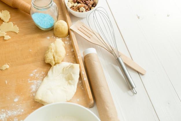 調理器具の横にある木製の机の上に横たわっている新鮮な生地のクローズアップ写真