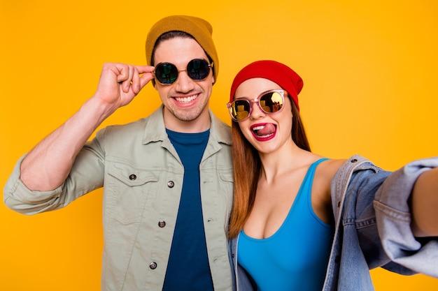 펑키한 미친 여자 젊은 부부가 함께 셀카를 만드는 멋진 젊은이들이 휴가를 즐기는 캐주얼 여름 옷을 입고 밝은 노란색 배경에 격리된 사진을 닫습니다
