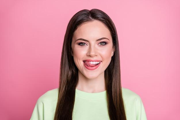 우스꽝스러운 매력적인 여성의 스트레이트 긴 머리 재미있는 소녀 같은 입술 혀의 클로즈업 사진은 맛있는 디저트가 캐주얼한 녹색 스웨터 풀오버 격리된 분홍색 배경을 입고 있는 것을 봅니다.