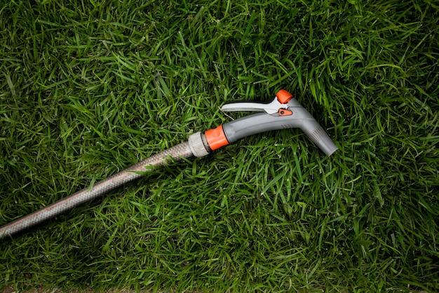 Крупным планом фото садового шланга, лежащего на свежей зеленой траве