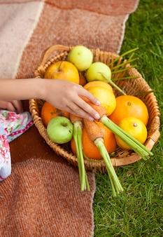 Крупным планом фото девушки, держащей корзину с фруктами и овощами