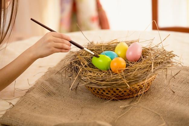 Крупным планом фото девушки, держащей кисть раскраски пасхальные яйца