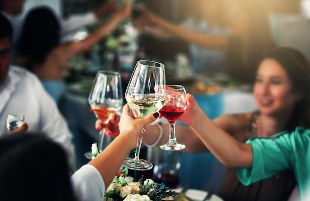 パーティーでワインとグラスをチリンと鳴らす手のクローズアップ写真