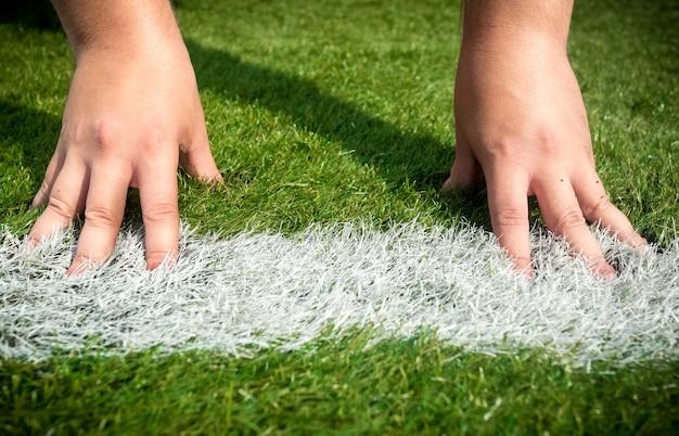 Крупным планом фото рук на белой стартовой линии, нарисованной на траве