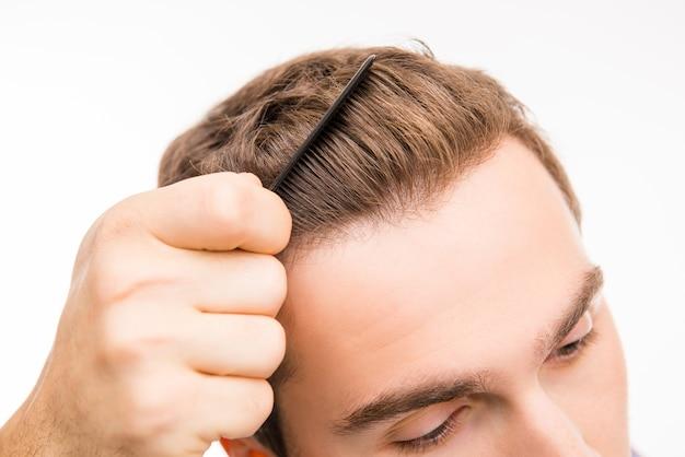 Крупным планом фото красивого молодого человека, расчесывающего волосы
