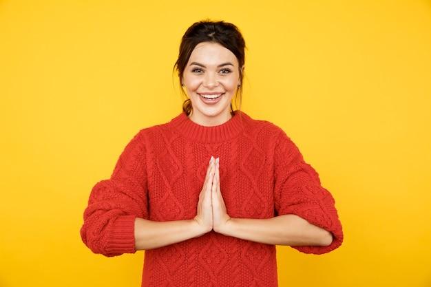 黄色のスタジオで希望に満ちた女性のクローズアップ写真。