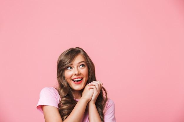 ピンクの背景に分離されたcopyspaceをよそ見と一緒に喜んで手を繋いでいる長い巻き毛の茶色の髪とうれしそうなきれいな女性のクローズアップ写真