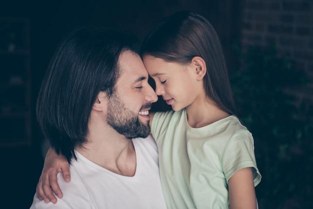小さな愛らしい女の子のクローズアップ写真夢のような笑顔の目を抱き締めるハンサムな若いパパ閉じたタッチ鼻は週末の時間を過ごす愛の雰囲気家の部屋屋内