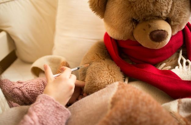 病気のテディベアに注射をしている少女のクローズ アップ写真