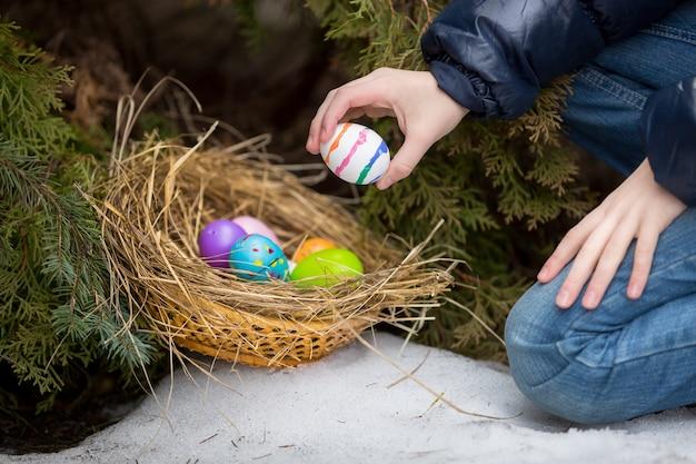 Крупным планом фото маленькой девочки кладет пасхальное яйцо в гнездо в холодный снежный день