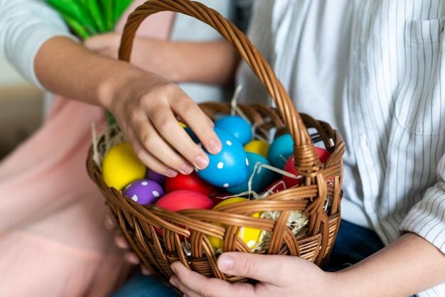 부활절 달걀 둥지에 퍼 팅하는 어린 소녀의 근접 촬영 사진.