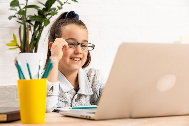 小さなかわいい生徒の学校の女性のオンラインレッスンビデオ通話のクローズアップ写真座って机