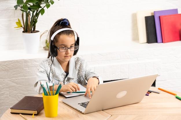 小さなかわいい生徒の学校の女性のクローズアップ写真は、オンラインレッスンのビデオ通話を話します