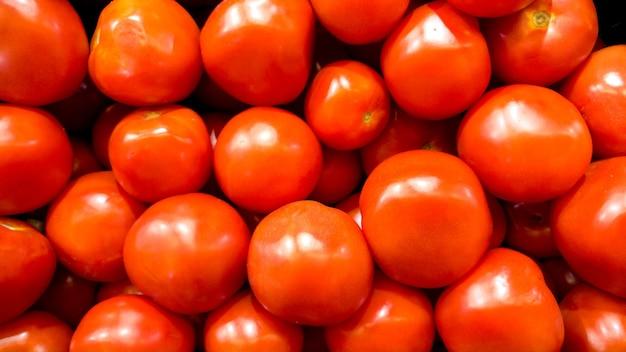 Крупным планом фото много свежих спелых помидоров. текстура или узор из свежих спелых овощей