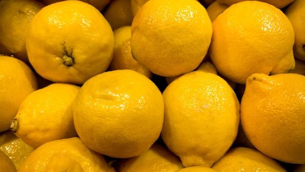 たくさんの黄色いレモンのクローズアップ写真。新鮮な熟した果物のクローズアップテクスチャまたはパターン。美しい食品の背景