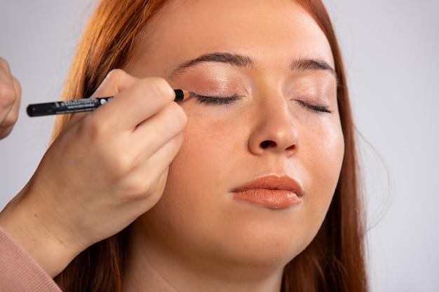 赤毛の女性の目を閉じてアイライナー化粧ペンシルの美しさを補うのクローズアップ写真
