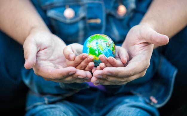 地球儀で女の子の手を繋いでいる男のクローズ アップ写真