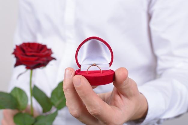 Крупным планом фото человека в формальной одежде, держащего розу