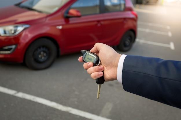 원격 자동차 경보 시스템에서 버튼을 누르는 사람의 근접 촬영 사진