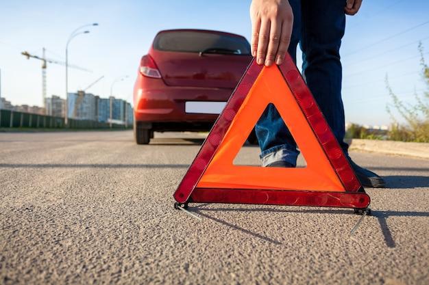 道路に三角形の警告標識を置く男のクローズ アップ写真