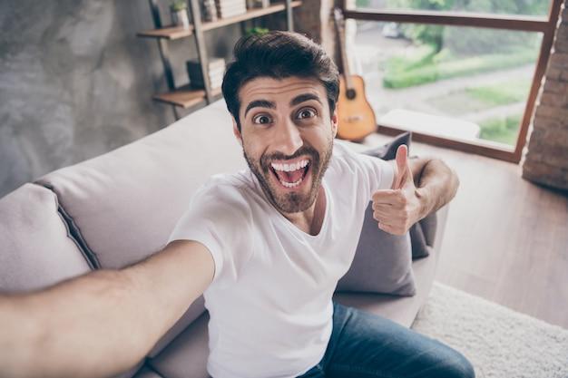 아늑한 소파에 앉아있는 혼혈 아랍 남자의 근접 촬영 사진은 계약 흥분된 착용 캐주얼 복장 플랫 로프트 거실 실내를 표현하는 엄지 손가락을 올리는 셀카 만들기