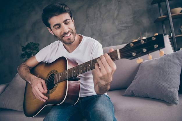 혼혈 남자가 앉아있는 소파의 근접 촬영 사진은 새로운 서면 노래 소리를 연주하는 어쿠스틱 기악 기타를 잡고 그의 취미 창조적 재능있는 사람 평면 로프트 거실 실내를 사랑합니다.