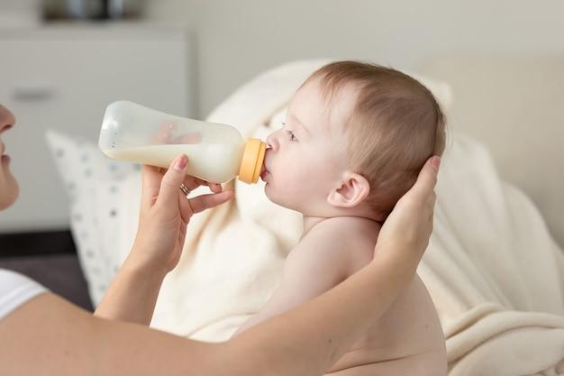 소파에 앉아 그녀의 아기 아들에게 병에서 우유를주는 어머니의 근접 촬영 사진