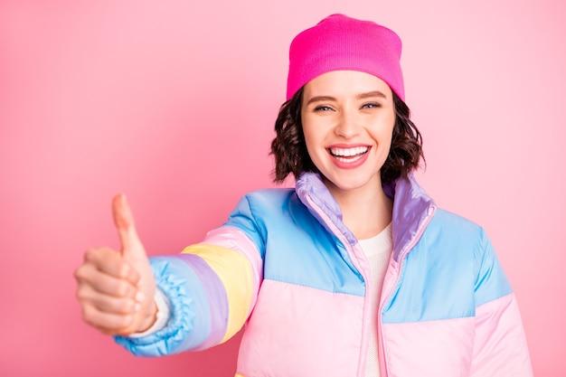 Крупным планом фото милой дамы, одобряющей прохладную новинку, одетую в теплое цветное пальто, изолированный розовый фон