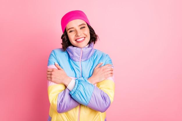 Крупным планом фото милой дамы, держащей теплые цветные пальто на розовом фоне