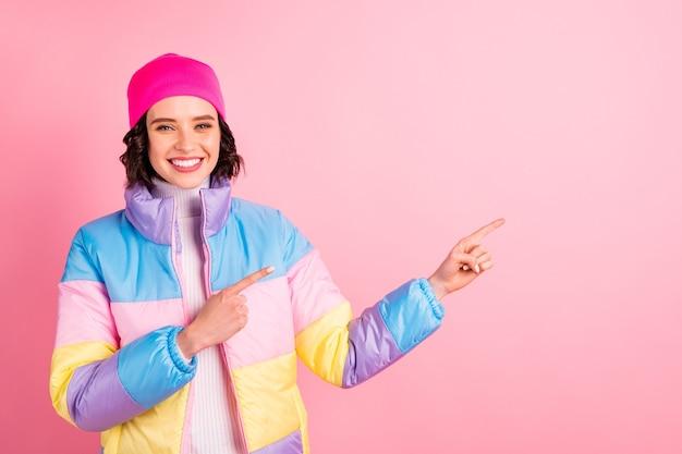 Крупным планом фото милой дамы, показывающей руки, пустое пространство, носить теплое цветное пальто, изолированный розовый фон