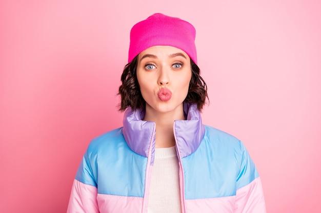 Крупным планом фото милой дамы, отправляющей воздушный поцелуй бойфренду, в теплом пальто на розовом фоне