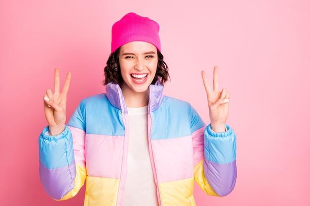 Крупным планом фото милой дамы, показывающей v-знак, носить теплое цветное пальто, изолированный розовый фон