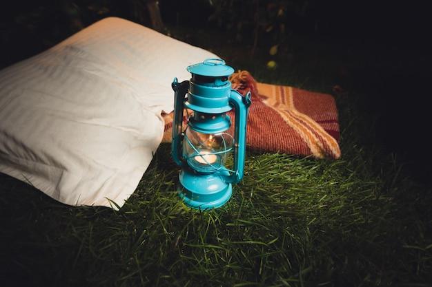夜に草の上に横たわる古いランタン、枕、毛布のクローズ アップ写真