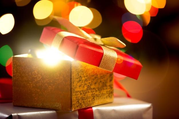 빛나는 조명 배경에 열린 크리스마스 선물 상자의 근접 촬영 사진