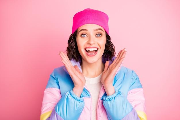 Фото крупным планом обрадованной удивительными новостями леди в теплом пальто на розовом фоне