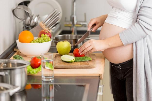 木の板で野菜を切る妊婦のクローズアップ写真