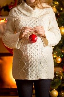 크리스마스 공 벽난로에 대 한 포즈 임신한 여자의 근접 촬영 사진
