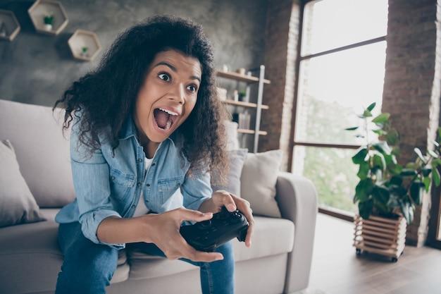 Крупным планом фото довольно темнокожей волнистой дамы, держащей джойстик консоли геймпада, увлеченного геймера, взволнованного, возбужденного, сидящего на удобном диване, повседневной джинсовой одежды
