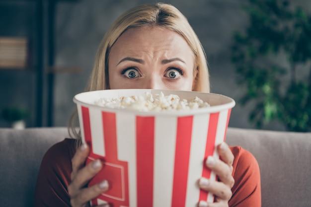 Крупным планом фото довольно забавной дамы, которая ест попкорн смотрит фильм ужасов, глаза полны страха, скрывая лицо, испуганное сидение на диване, повседневная одежда, плоская гостиная в помещении