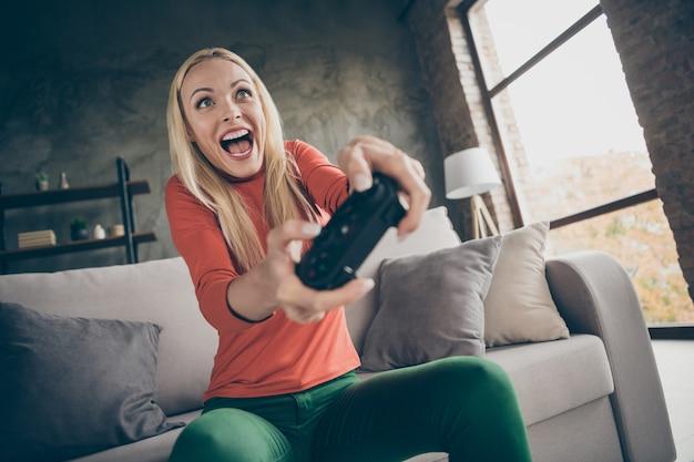 Крупным планом фото довольно забавной дамы, держащей геймпад, консольный джойстик, увлеченного геймера, взволнованного, открытого рта, хочу победы, сидя на удобном диване, повседневная одежда, гостиная в помещении