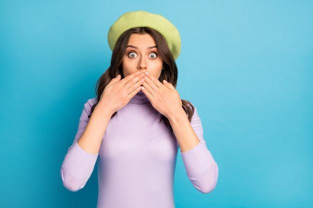 예쁜 아가씨의 근접 촬영 사진은 두려움으로 가득한 말문이없는 눈을 겁에 질린 숨어있는 입 비명 착용 녹색 베레모 모자 보라색 터틀넥 절연 파란색 벽
