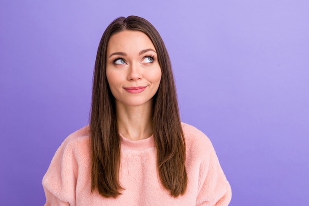 Крупным планом фото симпатичной леди, мечтательно выглядящей пустым пространством на стене фиолетового цвета