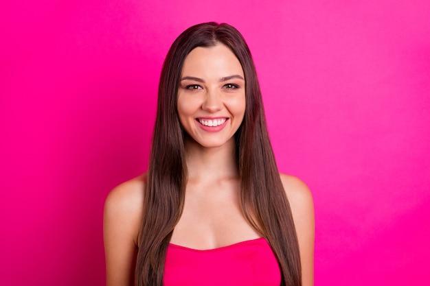 Крупным планом фото симпатичной дамы с удивительной длинной прической и очаровательной улыбкой, одетой в красивый топ с открытыми плечами, изолированный яркий розовый цвет фона
