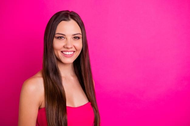 Крупным планом фото красивой дамы с удивительной длинной прической и очаровательной улыбкой в ярком топе с открытыми плечами, изолированном ярким розовым цветом фона