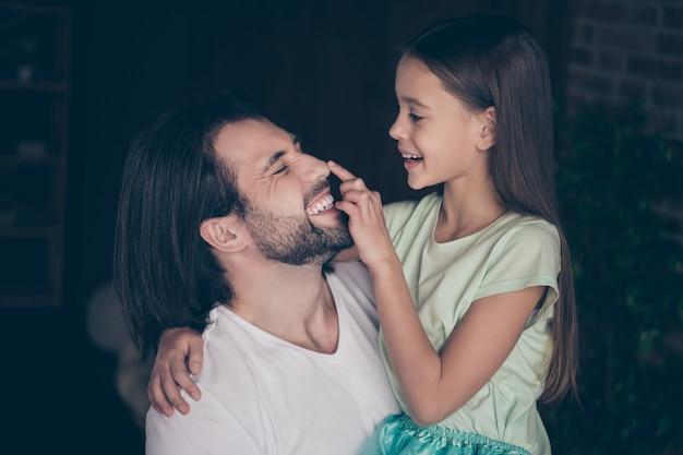 かわいい愛らしい女の子のクローズアップ写真ハンサムな若いパパは笑顔のタッチ鼻の指を抱き締めて週末の時間を家庭的な家庭的な雰囲気の家の部屋で過ごす