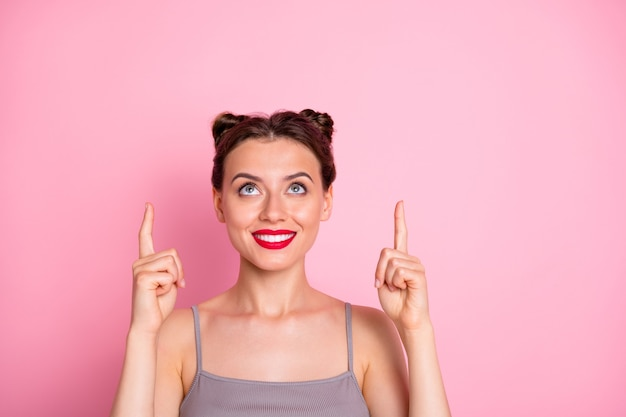 Крупным планом фото симпатичной миллениальной леди смешные булочки с красной помадой, указывающие пальцами вверх пустое пространство, лучшие цены на покупки, носить повседневную серую майку изолированного розового цвета