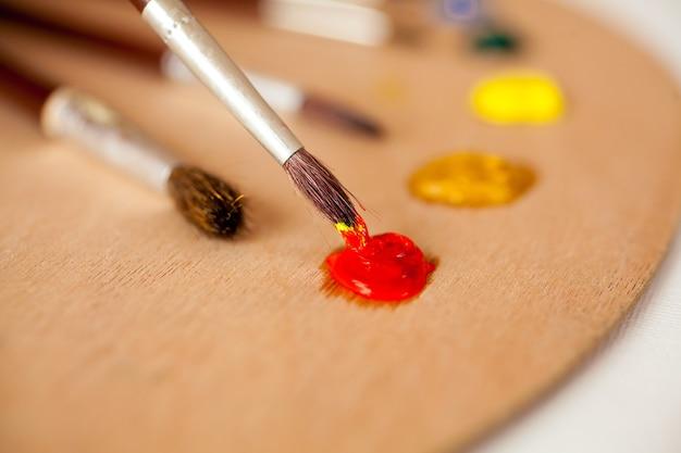 Крупным планом фото профессиональной кисти, смоченной красной масляной краской на палитре